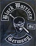 """Kombination aus den vier Komponenten Toprocker (oben) mit dem Schriftzug """"Black Warriors"""", Center-Patch (Mitte) mit einem stilisierten Schädel samt Augenmaske (Samurai-Kämpfer) und Samurai-Schwert, seitlichem Schriftzug (rechts) """"MC"""" sowie Bottomrocker (unten) mit dem Schriftzug """"Germany""""."""